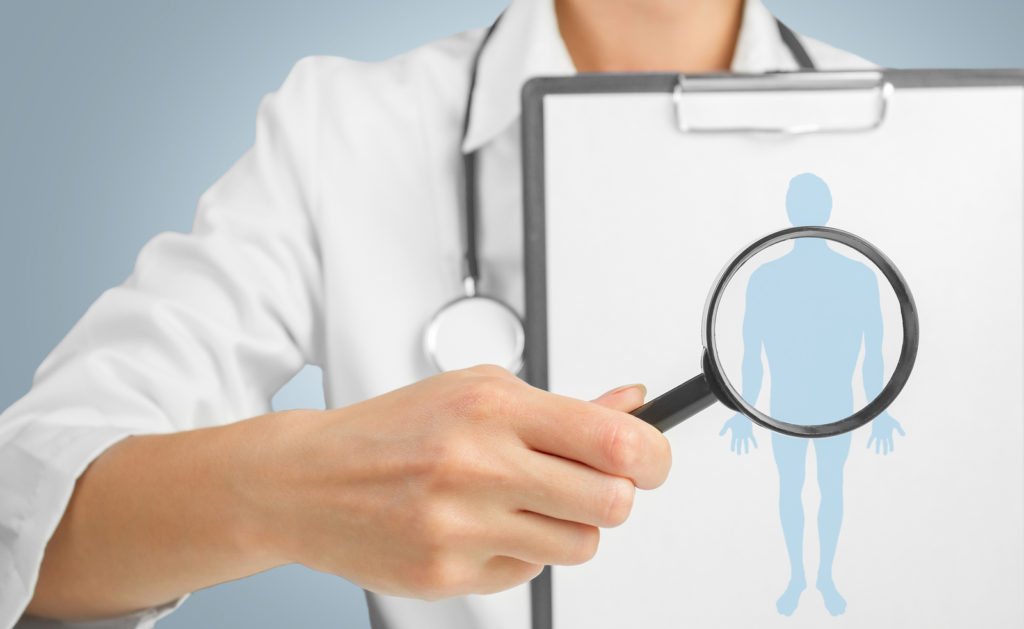 doctor is showing board with silhouette of a man under the medical magnifying glass